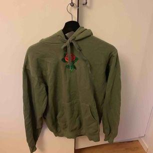 En olivgrön hoodie med en ros på. Snygg och bekväm, sitter bra. Inte för oversized men inte för tajt. Köpt för 350kr av ett lokalt företag. Köpare står för frakt ☺️