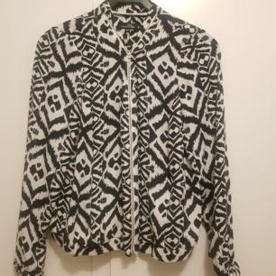 Nyskick glansig tröja i zebra-mönster, guldig kedja.