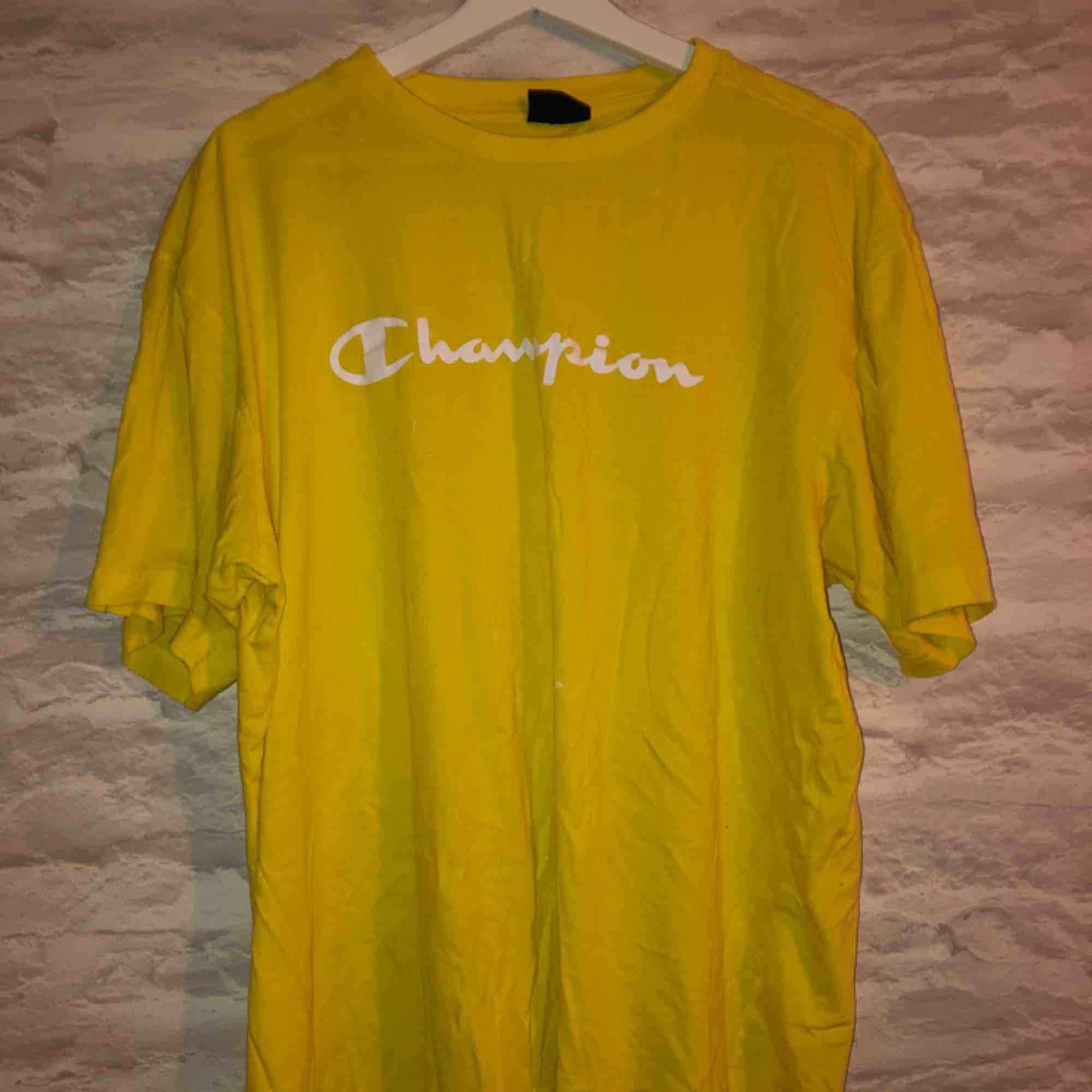 Gul champion t-shirt i storleken XXL men sitter som en L. Köparen står för frakten.. T-shirts.