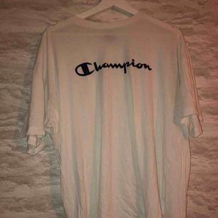 Vit champion t-shirt i storleken XXL men sitter som en L. Köparen står för frakten.