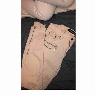 Ljusrosa/beiga jeans med detalj dragkedjor.