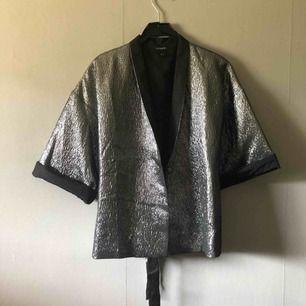 Silvrig kimono kavaj från Lindex som glittrar fint. Jag har haft armarna uppvikta som på bilden då jag tycker det är snyggare, men de går att vika ner och då är det silver hela vägen. Skärp i midjan så man kan knyta om man önskar. Använda en gång.