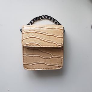 Beige väska med kort kedja samt justerbart och avtagbart band. Nyskick, oanvänd!   Säljer även en likadan i svart. 100 kr/st men vid köp av BÅDA får du de tillsammans för 130 kr.   Du står för frakt om du inte kan mötas upp i Stockholm.