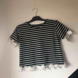 Svart och vit randig t-shirt med fina blomsterdetaljer. Lite croppad och bredare i modellen. Fint skick. Frakt tillkommer.
