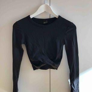 """Kort svart långärmad topp med """"omlott"""" från Gina Tricot. Mjukt material. Aldrig kommit till användning. Frakt tillkommer."""