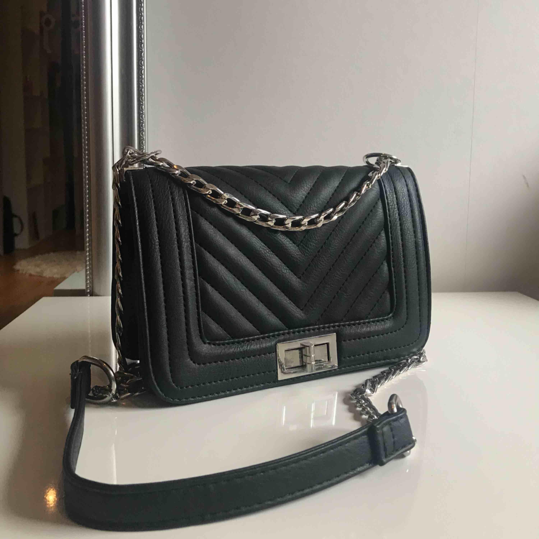 Superfin svart handväska! Använd ett extremt fåtal gånger och är i helt nyskick! Säljs då jag är en guldtjej och inte trivs med silverdetaljerna. Frakt tillkommer. . Väskor.