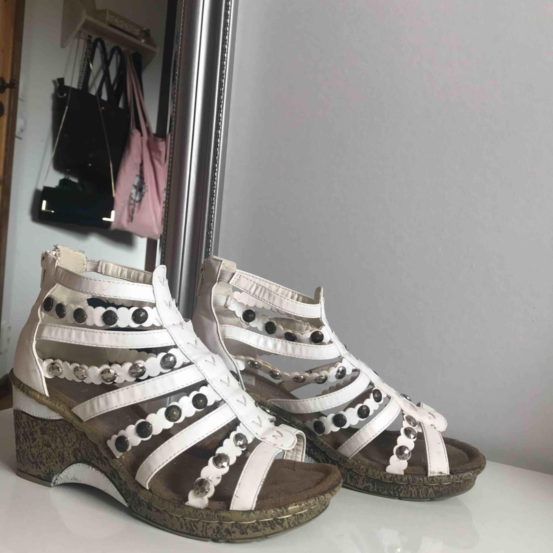 Vita sandaler med kilklack. Använda fåtal gånger. Säljs då jag inte trivs i klackar. Frakt tillkommer. . Skor.