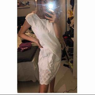 En vit klänning med fina detaljer! Går ner till knäna.