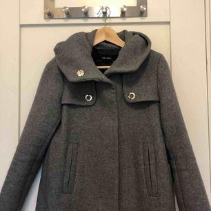 Superfin grå kappa med luva från Zara. Använd en gång och i perfekt skick! Säljer p.g.a använder ej. Priser går att förhandla.