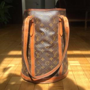 Säljer min älskade Louis Vuitton Bucket GM Monogram väska. Superbra skick och inköpt i Japan! 100% äkta. Serienummer för Louis Vuitton väskor är lätt att kolla upp på Google dessutom! AR0917 är koden (man ser den ej så väl inne i väskan längre). Har kvitto/äkthetsintyg från affären osv! Inga skambud, det svarar jag inte på! 🌷 Skriv inte heller om du inte är seriös.  Skickas rekommenderat (försäkrat). Skickar även bild medans jag slår in paketet osv!