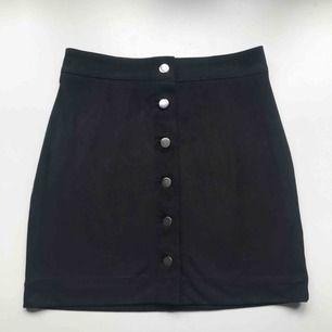 Frakt ingår! • svart minikjol i svart mjukt mocka-inspirerat material med silvriga knappar framtill • från H&M i storlek36 • i bra skick!