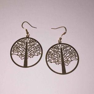 ett par såå coola guldiga örhängen med träd ! köpta för 80kr och aldrig använda!