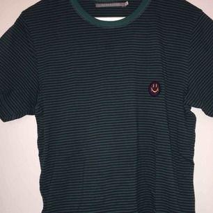 säljer en ball t shirt! grön och svartrandig med lila smiley på! köpt på carlings , men märket är HOMEBOUND.