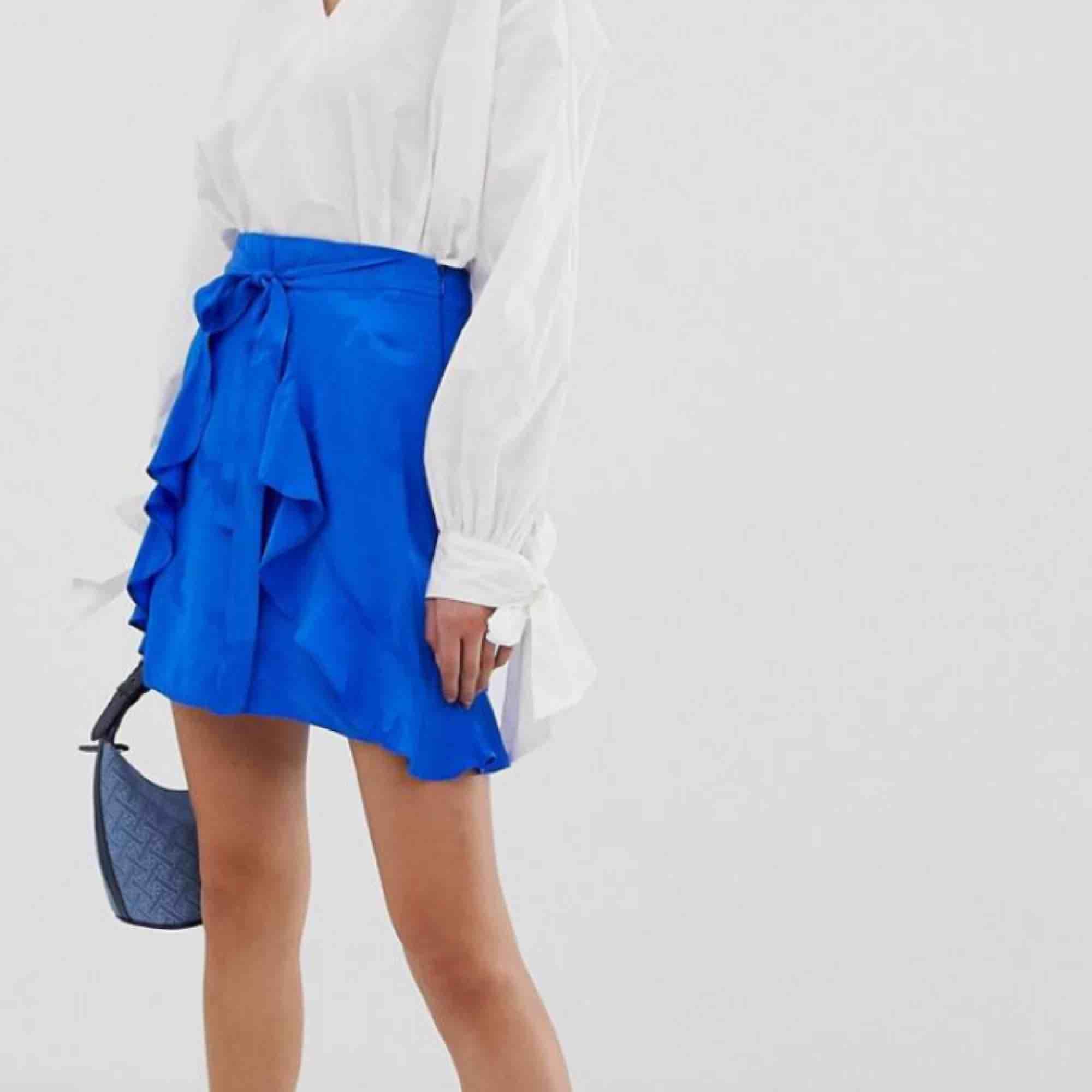 Blå wrap kjol i satin liknade material, endast använd fåtal gånger. Frakt 50kr😊. Kjolar.