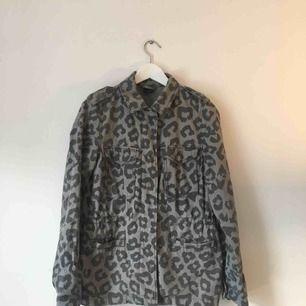 Tunn och bekväm höst eller vår- jacka. Grått leopardmönster och fickor på sidan.