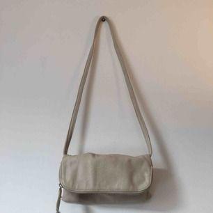 En liten beige väska ( liknande kuvertväska ). Aldrig använd men lite sliten i dragkedjan.