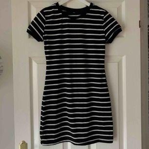 Svart klänning med vita sträck, figur sydd. Liten i storlek så skulle säga att den är mer S än M. Använd 1 gång
