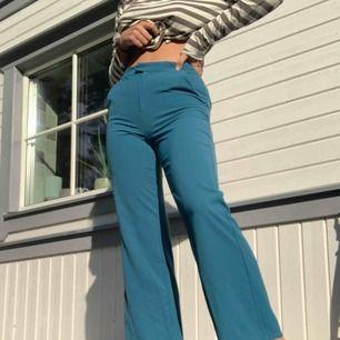 Ett par turkosa kostymbyxor. De sitter lagom tight runt rumpa och lår men svänger ut längs smalbenen. Säljer pga en aning korta på mig (173 cm lång).