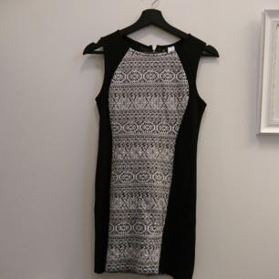 Kort figurnära klänning i lätt elastiskt tyg. DIVIDED by H&M. Kort dragkedja i nacken. Sidostycke: 73% Polyester, 21% viskos, 6% elastan. Yttertyg: 54% bomull, 45% Polyester, 1% elastan. Maskintvätt 30°.