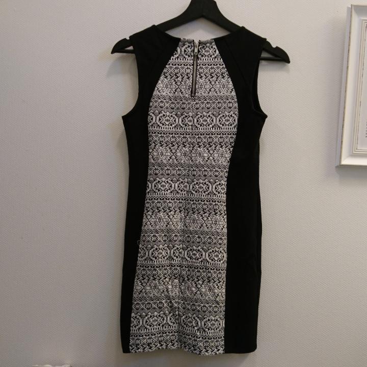 Kort figurnära klänning i lätt elastiskt tyg. DIVIDED by H&M. Kort dragkedja i nacken. Sidostycke: 73% Polyester, 21% viskos, 6% elastan. Yttertyg: 54% bomull, 45% Polyester, 1% elastan. Maskintvätt 30°. . Klänningar.