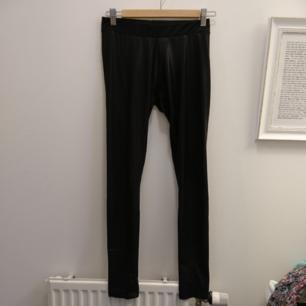 Svarta glansiga leggings. Passar till exempel till en festlig tunika eller klänning. 91% Polyester, 9% elastan. Maskintvätt 30°.
