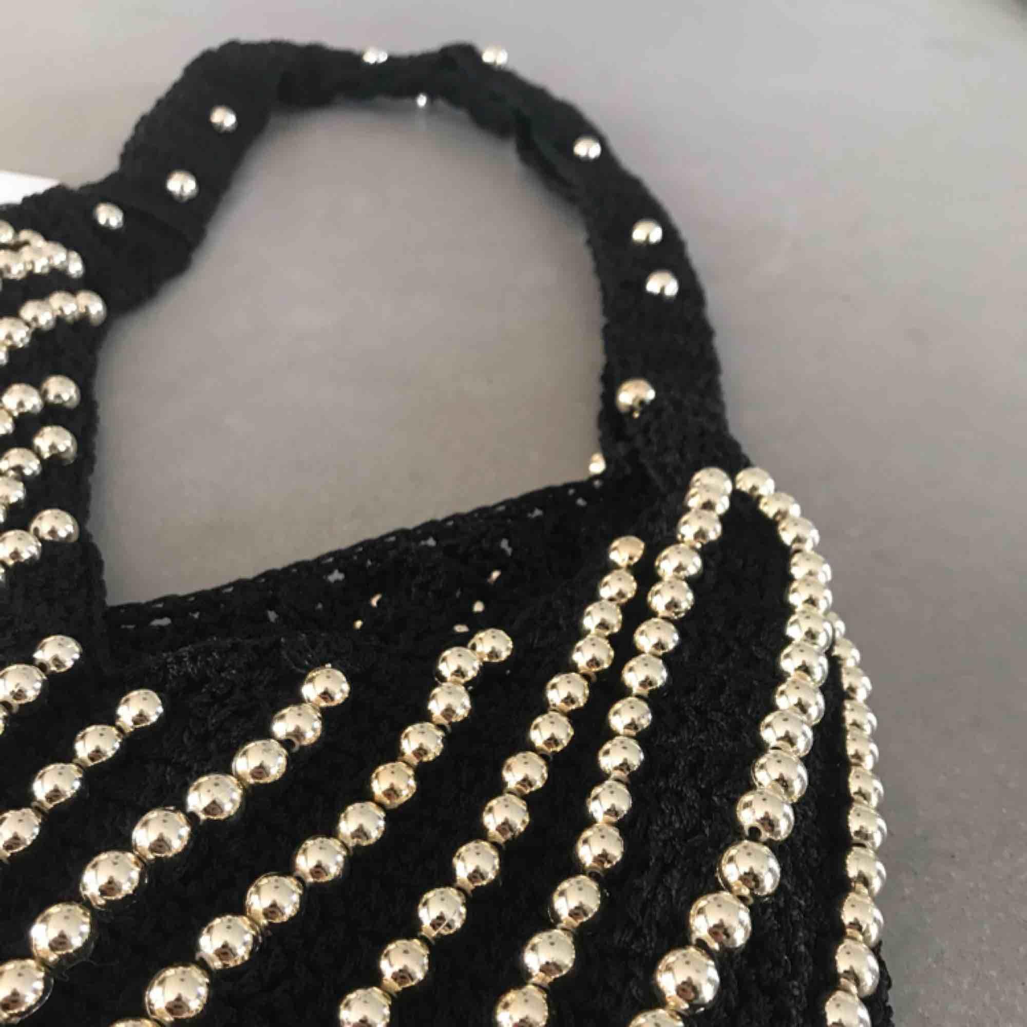 Påsväska i svart virkning med guldpärlor. Aldrig använd och alldeles ny (nypris 350 kr). Mått: Höjdxbredd - 31x25,5 cm. Köparen står för frakt. Väskor.
