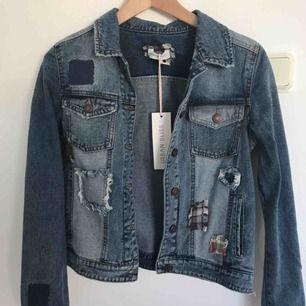 """Blå jeansjacka med detaljer i form av påsydda """"lappar"""". Aldrig använd. Köpt från asos. Köparen står för frakt."""