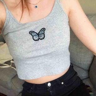 🦋Världens sötaste linne! Det är grått och croppat och har en super söt blå fjäril på bröstet. Jag har knytit banden då de var för långa på mig, men knuten går såklart att ta upp! 150kr inkl frakt! 🦋