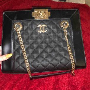 En Chanel kopia som jag köpte för något år sedan. Nästan aldrig använd och i bra skick, säljer den för att jag inte får någon användning av den i vardagen. Bredd:31cm Höjd: 25cm Köparen står för frakten:)