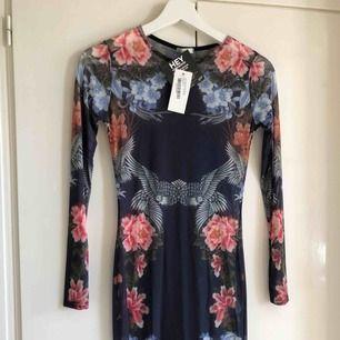 Oanvänd transparent klänning med mönster från Nelly. Köparen står för frakt!