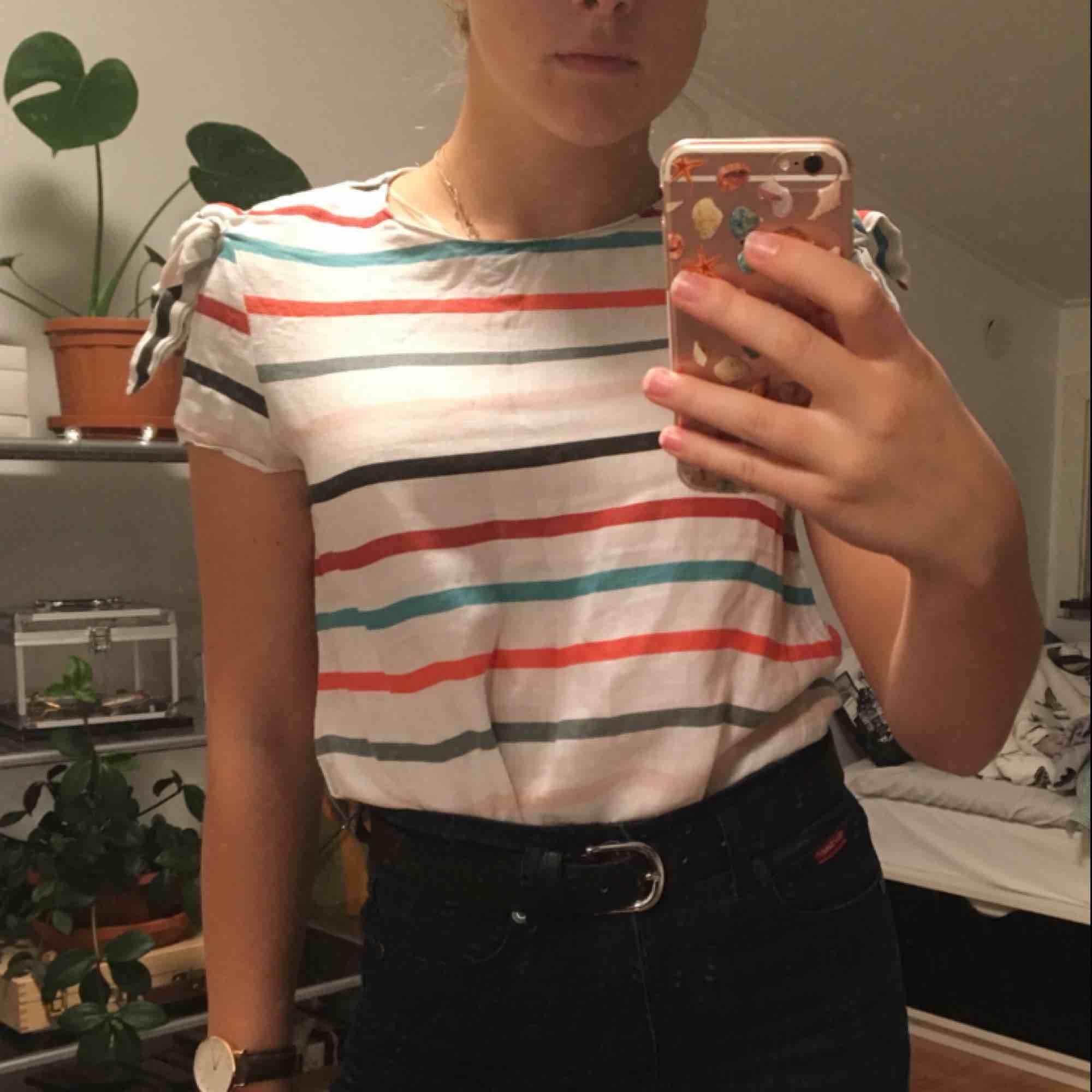 Vit t-shirt med gröna, orangea och svarta ränder från Zara. Med rosetter på axlarna. 100% linnen. Priset är inkluderat frakt.. T-shirts.