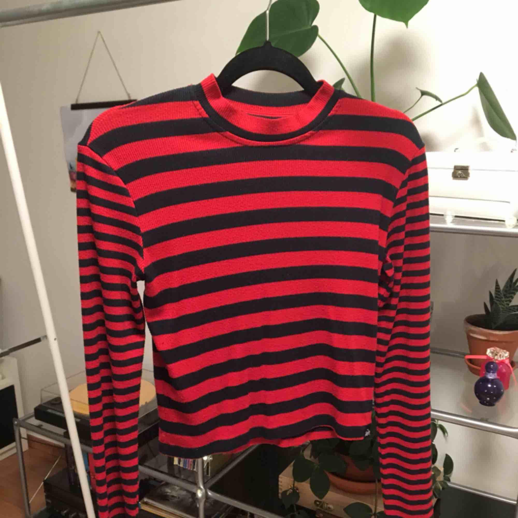 En långärmad tröja från Superdry. Lite räfflat tyg med svarta och röda ränder. Liten polokrage. Priset är inkluderat frakt.. Tröjor & Koftor.
