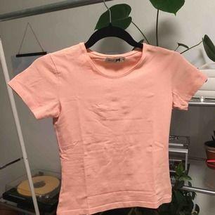 En vanlig gullig t-shirt som är ungefär ljusrosa/persika färgad. Använd två gånger. Priset är inkluderat frakt.