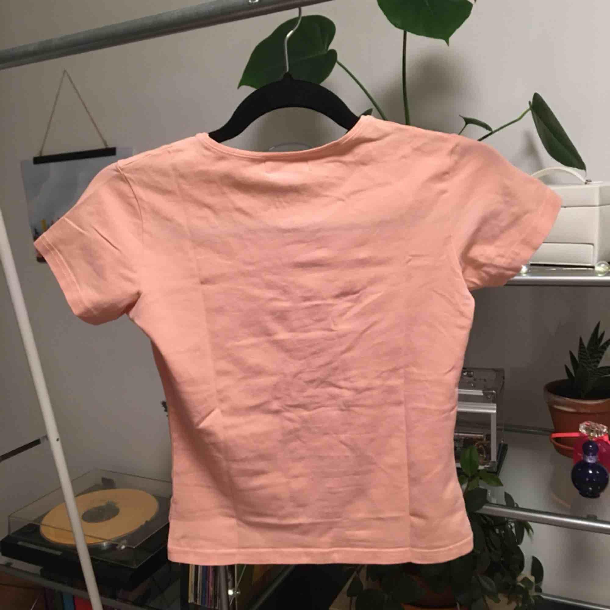En vanlig gullig t-shirt som är ungefär ljusrosa/persika färgad. Använd två gånger. Priset är inkluderat frakt.. T-shirts.
