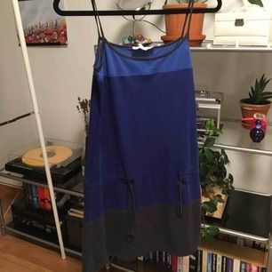 En blå/mörkblå/grå klänning med ett spänne runt höfterna. Perfekt att gå till stranden med eller ha över en långärmad tröja eller t-shirt.