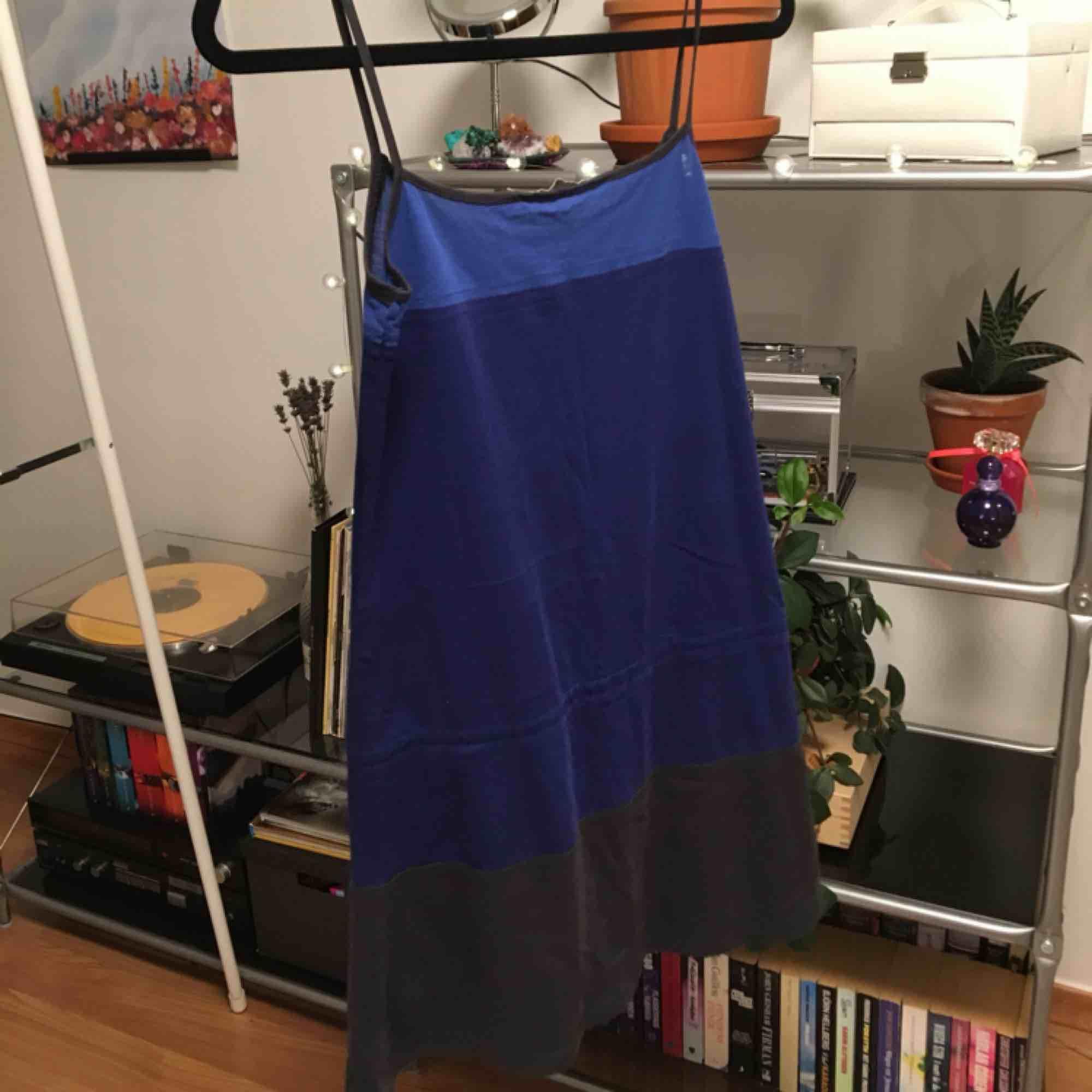En blå/mörkblå/grå klänning med ett spänne runt höfterna. Perfekt att gå till stranden med eller ha över en långärmad tröja eller t-shirt. Priset är inkluderat frakt.. Klänningar.