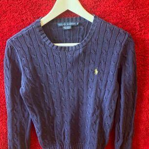 En Marinblå Ralph Lauren stickad tröja. Märket är gult.  Använt tröjan max 3 gånger och är nästan som ny, köpt för 1200 . Storlek M  Köparen står för frakten.