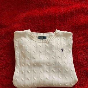 En vit Polo Ralph Lauren stickad tröja.  Finns ett hål i högra armhålan men går att sy. Märket är marinblå. Använt tröjan några gånger och är nästan som ny, köpt för 1200 och säljer för 250 köparen står för frakten.