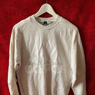 En grå vit Adidas hoodie Märket är vitt och har dragkedja på båda sidorna  Storlek M Köparen står för frakten