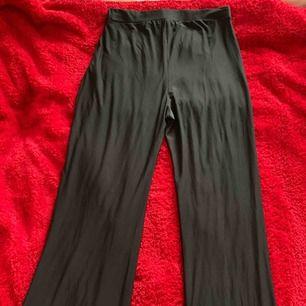 Ett par utsvängda svarta byxor från Nelly. Byxorna säljs som ett sätt men jag säljer bara byxorna. Storlek M  Köparen står för frakten