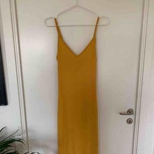 Skitsnygg tajt gul klänning med slit i sidan