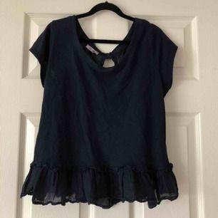 Fin marinblå T-shirt blus från Tessie med volang nedtill och knappar i ryggen. Fint skick. Står ej storlek men skulle gissa på xs/s. Köparen står för frakt