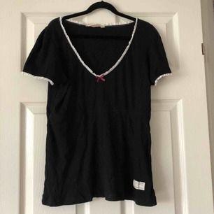 Svart oddmolly T-shirt, vit spets, rosa rosett. Fint skick. Storlek 2. Köparen står för frakt.