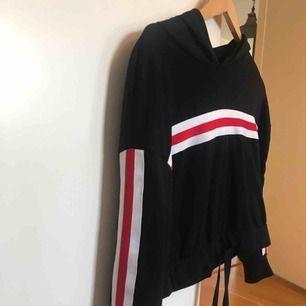 Svart hoodie med rödvita streck i strl XS