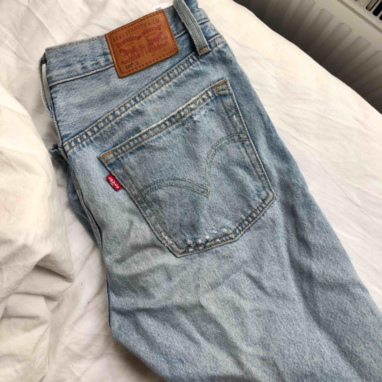 ljusblå jeans från Levis i W26/L28, hål på båda knäna, tighta vid rumpan mer pösiga nere vid vaderna. Sparsamt använda. Jeans & Byxor.