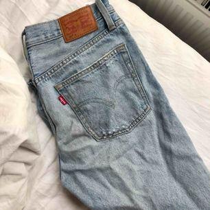 ljusblå jeans från Levis i W26/L28, hål på båda knäna, tighta vid rumpan mer pösiga nere vid vaderna. Sparsamt använda