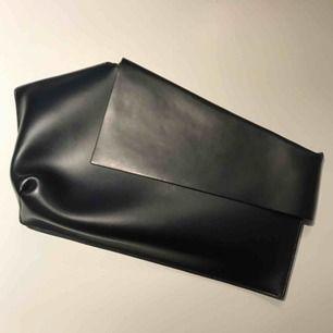 Handväska i läder från Weekday. Asymmetrisk cool design. Välanvänd men i fint skick! Tyvärr inget band kvar till väskan, men supersnygg att ha som kuvertväska också:)