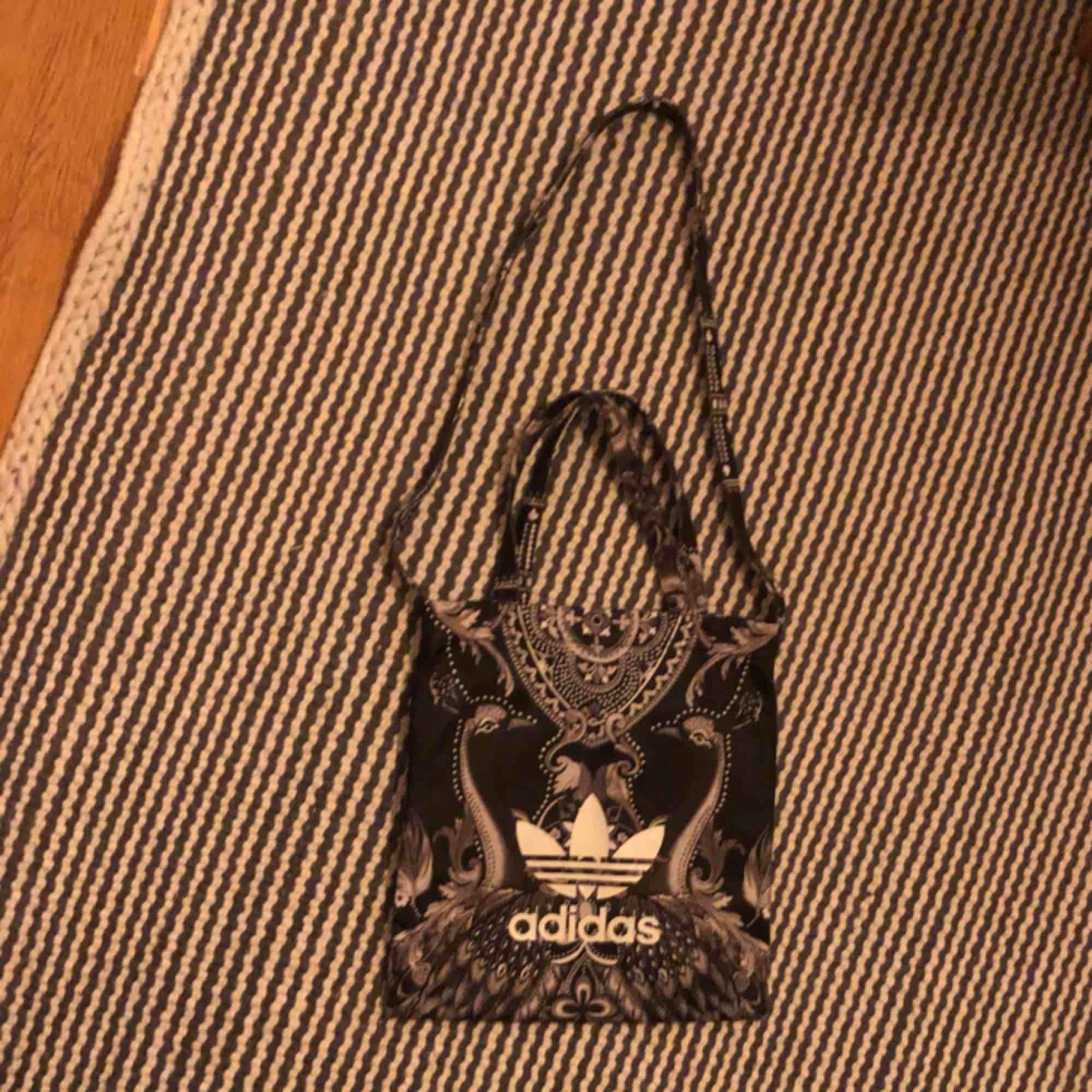 """en väska med coolt mönster och med trycket """"adidas"""". använd fåtal gånger🧡 säljer då den inte kommer till användning längre. den lilla frakten står du för❤️💕. Väskor."""