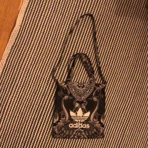 """en väska med coolt mönster och med trycket """"adidas"""". använd fåtal gånger🧡 säljer då den inte kommer till användning längre. den lilla frakten står du för❤️💕"""