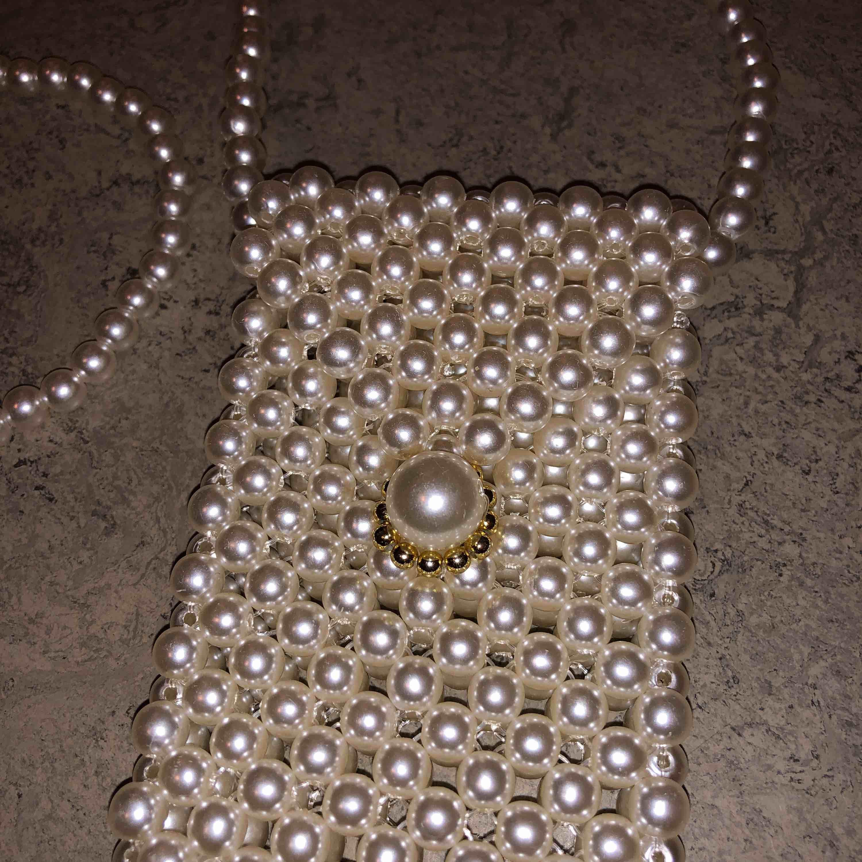 Liten vit pärlväska med fin guldig detalj vid knäppningen. Frakt tillkommer🥰 OBS! Väldigt liten, får inte plats med telefonen . Väskor.